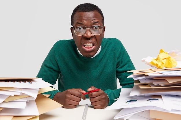 Funcionário do sexo masculino de pele escura aborrecido e sobrecarregado, ocupado com muito trabalho, cercado de pilhas de papéis, anotações para projetos, segura uma caneta, senta-se na mesa Foto gratuita