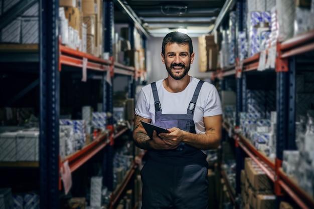 Funcionário trabalhador tatuado barbudo sorridente segurando o tablet e parado no armazenamento. Foto Premium