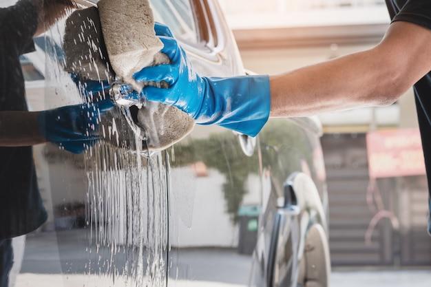 Funcionários da lavagem de carros usando luvas de borracha azul usando uma esponja umedecida em água e sabão para limpar o carro. Foto Premium