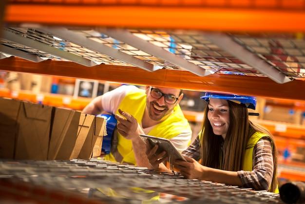 Funcionários do armazém contando caixas nas prateleiras de um grande armazém de distribuição Foto gratuita