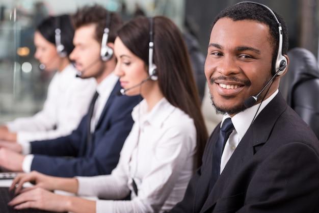Funcionários do call center estão sorrindo e trabalhando em computadores. Foto Premium