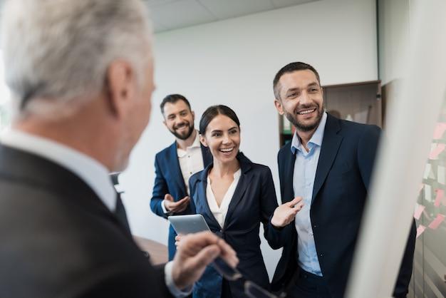 Funcionários e seu diretor estão ao lado do rack Foto Premium