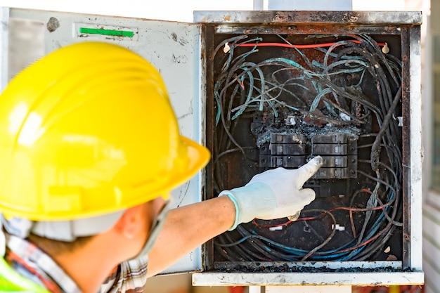 Funcionários que verificam a causa da placa de circuito de controle de incêndio Foto Premium