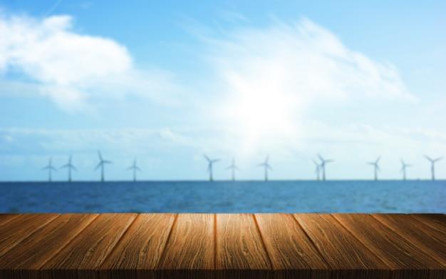 Fundo 3d de uma mesa de madeira com vista para um parque eólico no mar Foto gratuita