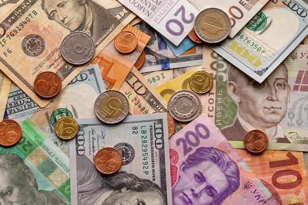 Fundo abstrato colorido feito de moedas diferentes do metal, de contas americanas, ucranianas e da moeda das notas de euro. dinheiro e finanças, conceito de investimento bem sucedido. Foto Premium