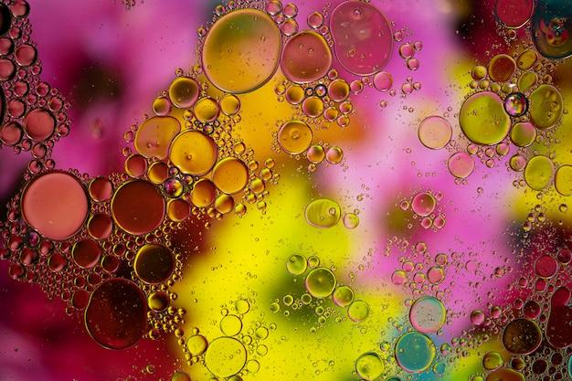 Fundo abstrato com cores vibrantes. o óleo cai na água. feche bolhas coloridas e artísticas. Foto Premium