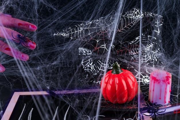 Fundo assustador de halloween com as mãos ensanguentadas, abóboras, teias de aranha, aranhas Foto Premium