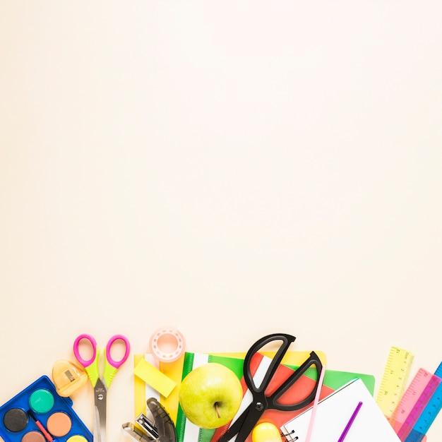 Fundo bege com material escolar Foto gratuita
