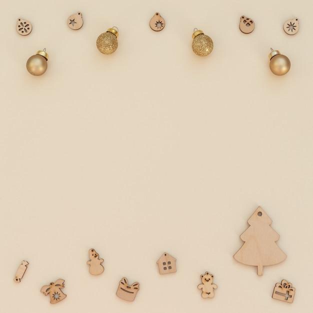 Fundo bege de natal com decoração de natal de madeira e bolas de natal douradas. estilo liso leigo com espaço de cópia. cartão de ano novo. Foto Premium