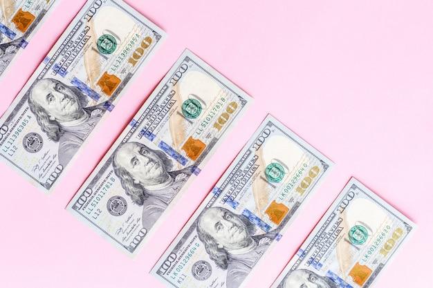 Fundo com as notas de dólar do americano cem do dinheiro do dinheiro isoladas no rosa. lay plana. vista do topo Foto Premium