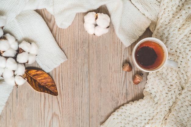 Fundo com blusas quentes e xícara de chá. ainda vida aconchegante em tons quentes. conceito de outono-inverno. Foto Premium