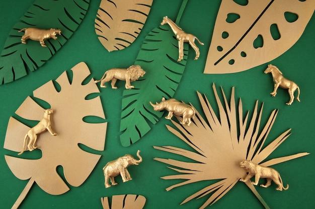 Fundo com folhas tropicais douradas e animais exóticos Foto Premium