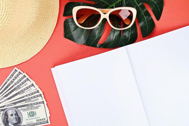 Fundo coral do bloco de notas, vidros de sol, chapéu, dinheiro. Foto Premium