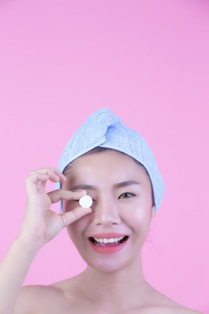 Fundo da cor-de-rosa da almofada da máscara protetora da jovem mulher. Foto gratuita