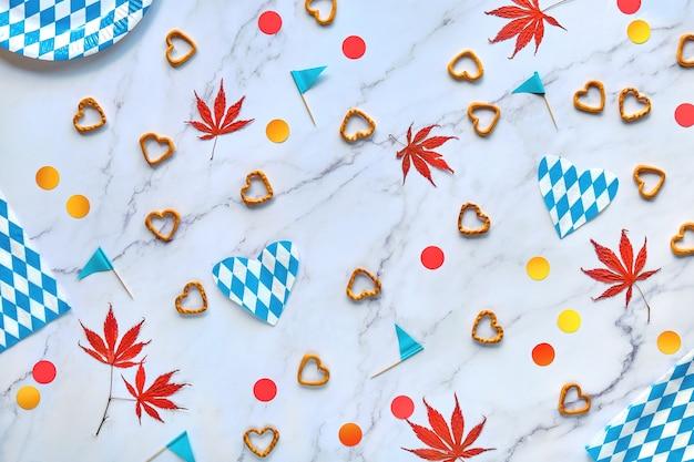 Fundo da festa oktoberfest. plano deitado na mesa de mármore. pratos de papel descartáveis quadriculados brancos azuis da baviera e bandeiras de papel. Foto Premium