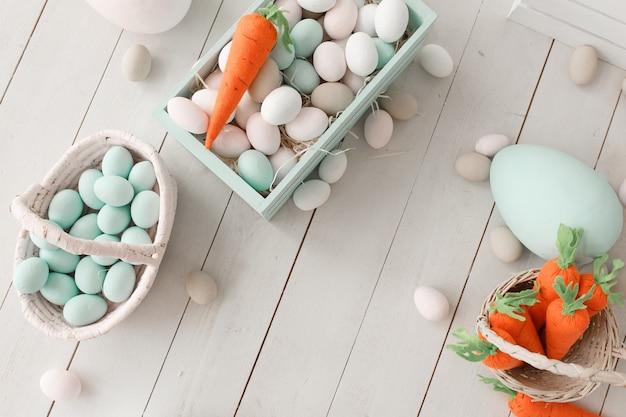 Fundo da páscoa com ovos coloridos e as cenouras alaranjadas amarelas sobre a madeira branca. Foto gratuita