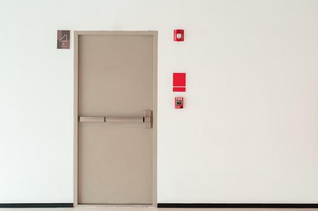 Fundo da porta de saída de emergência com a parede do espaço da cópia, prédio de escritórios interior Foto Premium