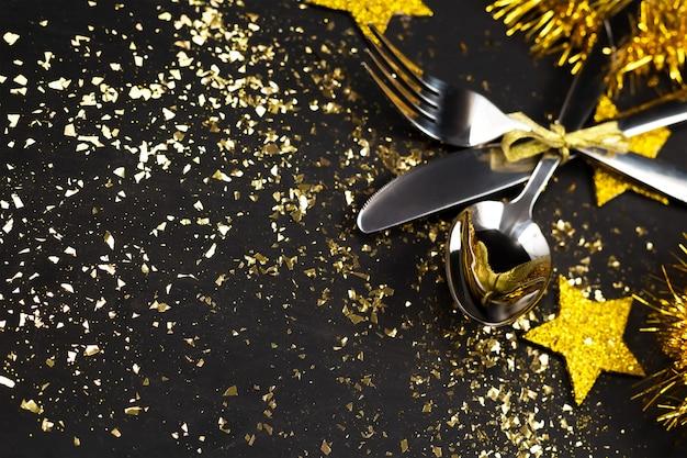 Fundo de ano novo. mesa preta com talheres, estrelas de ouro, ouropel, decoração de natal Foto Premium