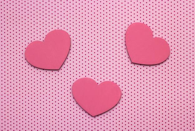 Fundo de bolinhas rosa e corações de madeira Foto Premium