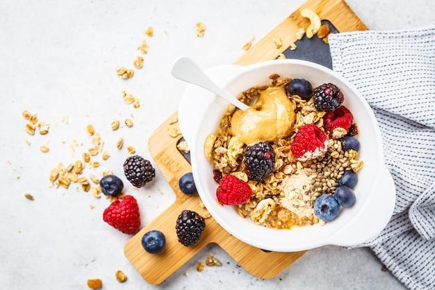 Fundo de comida de café da manhã. granola com sementes de cânhamo, pó de maca, manteiga de amendoim e frutas na mesa branca. Foto Premium