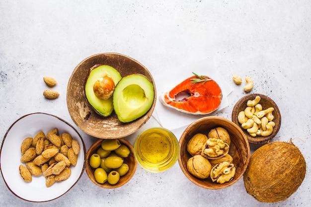 Fundo de comida gorda saudável. peixe, nozes, óleo, azeitonas, abacate, branco, fundo, topo, vista Foto Premium