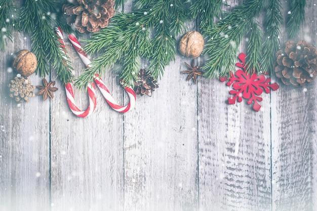 Fundo de composição de natal. doces doces varas, pinhas, ramos de abeto em madeira b Foto Premium