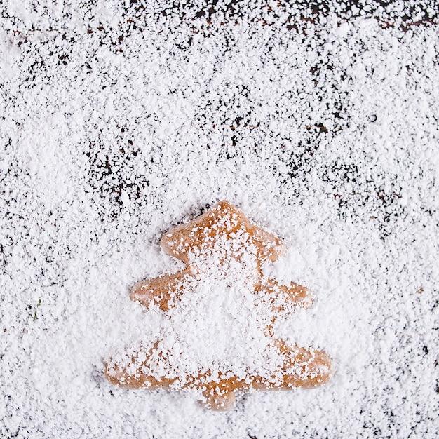Fundo de conceito de natal, pão artesanal em forma de uma árvore de natal em uma mesa de madeira, frustrada pela neve branca Foto Premium