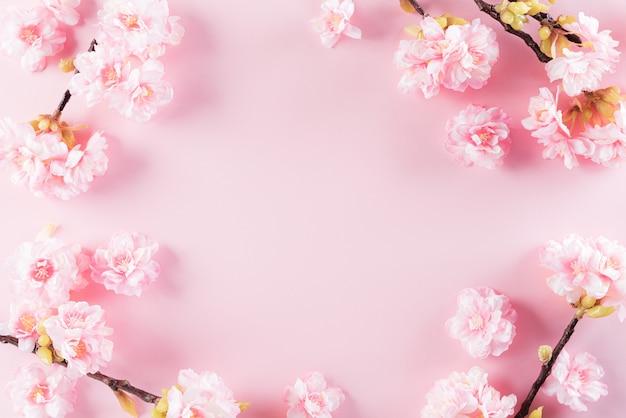 Fundo de cores rosa pastel com padrões de configuração plana de flores em flor. Foto Premium