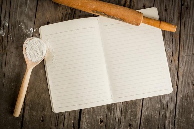 Fundo de cozimento. ferramentas e ingredientes para assar na velha mesa de madeira rústica. bloco de notas do livro para receitas. espaço de cópia da vista superior Foto Premium
