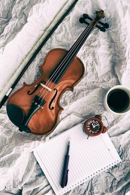 Fundo de desenho de arte abstrata de violino colocado ao lado do despertador vermelho e livro, na superfície do grunge Foto Premium