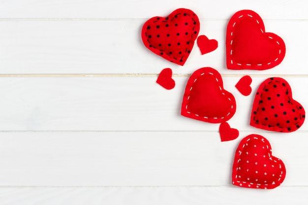 Fundo de dia dos namorados com corações de brinquedo feito à mão na mesa de madeira Foto Premium
