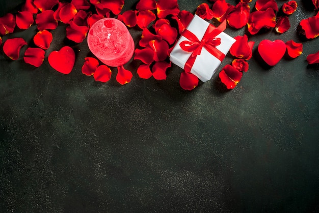 Fundo de dia dos namorados com pétalas de flores rosa, branco embrulhado caixa de presente com fita vermelha e vela vermelha de férias, no fundo escuro de pedra, cópia espaço vista superior Foto Premium