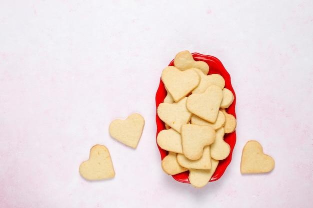 Fundo de dia dos namorados, corações de dia dos namorados em forma de biscoitos, vista superior Foto gratuita