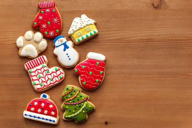 Fundo de férias de ano novo de natal, biscoitos de gengibre colorfull e cones na mesa de madeira. copie o espaço. conceito de férias. Foto Premium