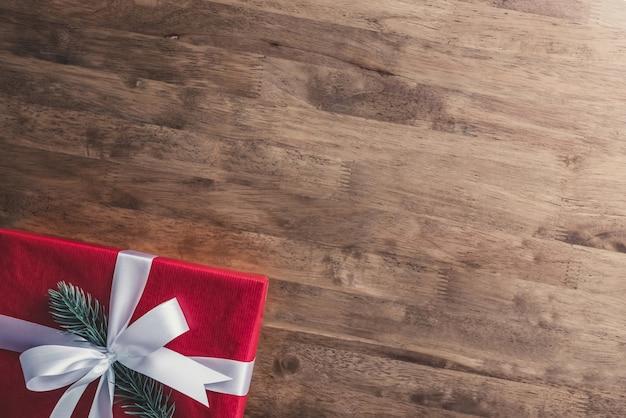 Fundo de férias de natal e ano novo com caixa de presente vermelha na mesa de madeira na fronteira Foto Premium