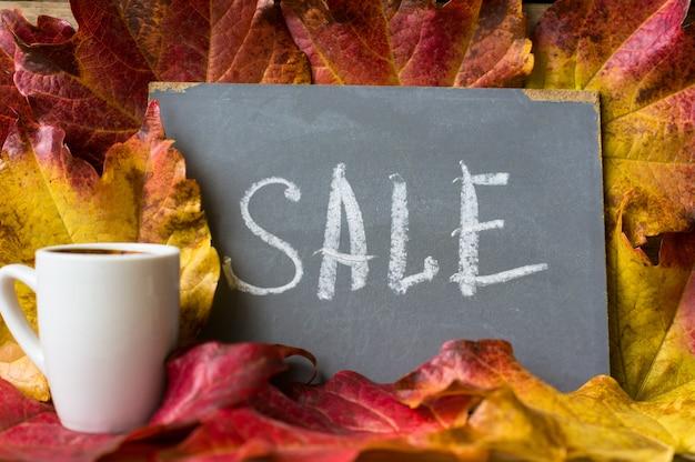 Fundo de folhas brilhantes outonais com quadro-negro e café Foto Premium