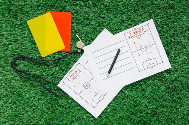 Fundo de futebol na grama com papel tático e cartões Foto Premium