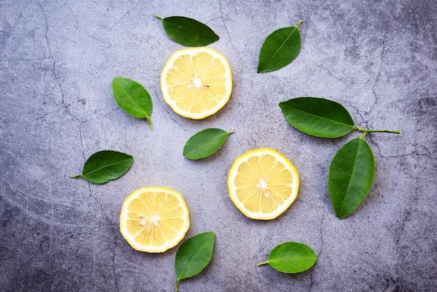 Fundo de limão / fatia de limão sem costura e folha verde no escuro Foto Premium