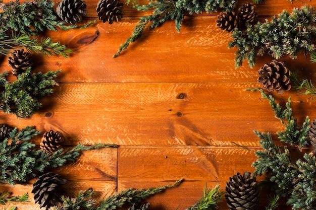 Fundo de madeira com moldura de cones de árvore de natal Foto gratuita