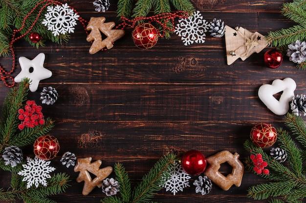 Fundo de natal, árvores de natal, brinquedos e pão de gengibre feitos à mão em uma mesa de madeira Foto Premium