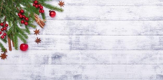 Fundo de natal com árvore do abeto e decorações vermelhas na mesa de madeira. faixa horizontal Foto Premium