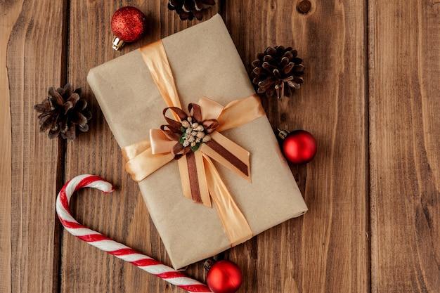 Fundo de natal com cones de natal e brinquedos, ramos de abeto, caixas de presente e decorações em um fundo de mesa de madeira Foto Premium