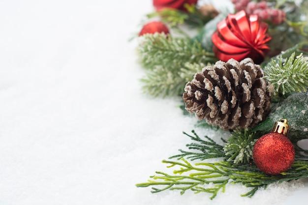 Fundo de natal com enfeites, ramos de abeto verde, pinhas, sobre fundo branco de neve. Foto Premium