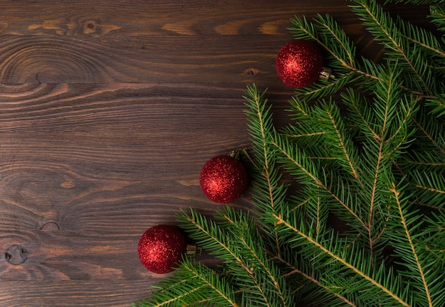 Fundo de natal com galhos de pinheiro e decorações na mesa de madeira velha marrom. espaço para texto ou desenho. vista do topo. Foto Premium
