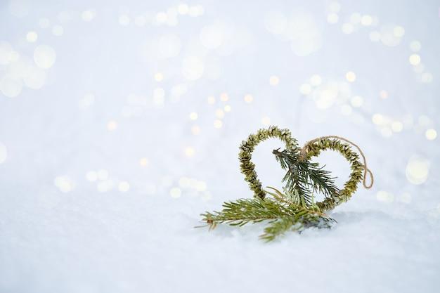 Fundo de natal coração feito de abeto na neve com bokeh Foto Premium