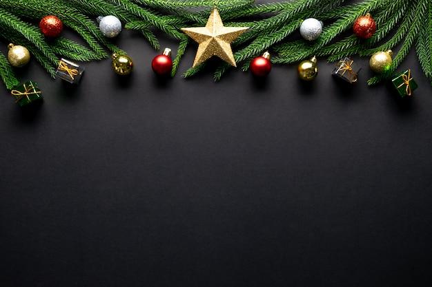 Fundo de natal. galhos de árvore do abeto, decorações vermelhas em fundo preto Foto Premium