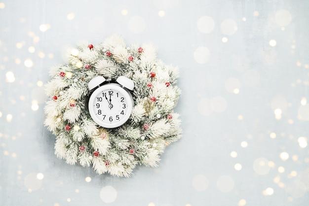 Fundo de natal. guirlanda de natal branca e despertador sobre fundo azul. copie o espaço para o texto Foto Premium