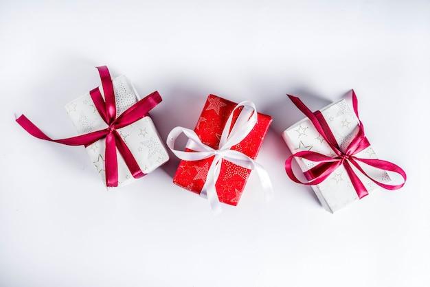Fundo de natal para cartão, com galho de árvore do abeto e caixas de presentes com fitas, na vista superior de fundo branco, cópia espaço para texto Foto Premium