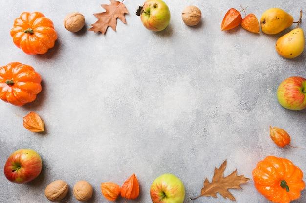 Fundo de outono com folhas amarelas, abóboras maçãs peras e nozes Foto Premium