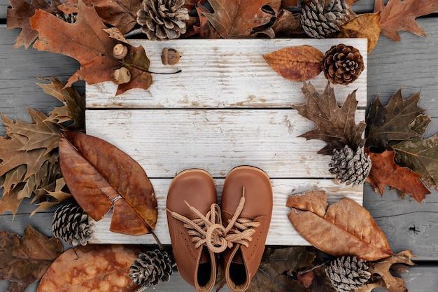 Fundo de outono com folhas naturais, pinhas e sapatos de couro em madeira envelhecida com espaço de cópia, conceito de férias de temporada Foto Premium